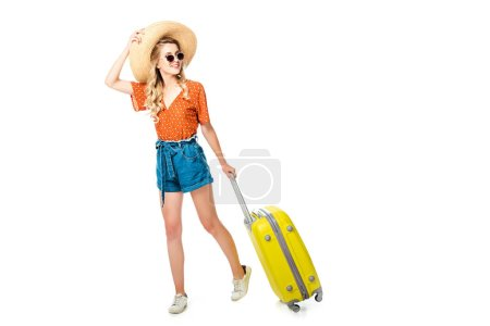 Photo for Young woman in sunglasses and straw hat with yellow suitcase isolated on white - Royalty Free Image