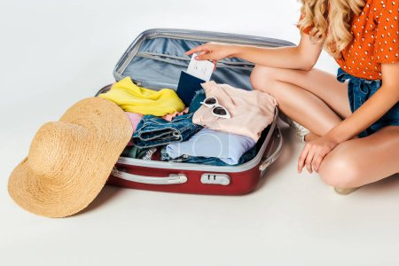 partial view of woman sitting at opened suitcase on white floor