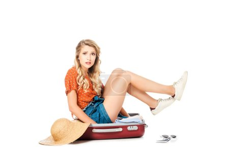 confused young woman trying to pack full suitcase isolated on white