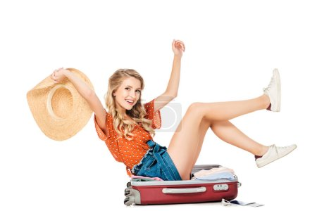 side view of smiling woman with straw hat in hand sitting in suitcase isolated on white