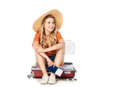 happy young woman in straw hat with passport and ticket sitting in suitcase isolated on white