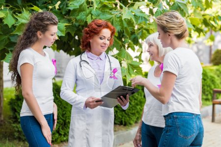 women with pink ribbons looking at doctor with clipboard, breast cancer awareness concept