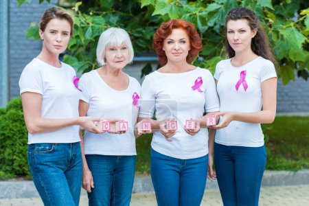 women with breast cancer awareness ribbons holding cubes with word cancer and looking at camera