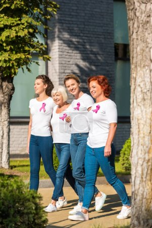 smiling women with breast cancer awareness ribbons holding hands and walking together