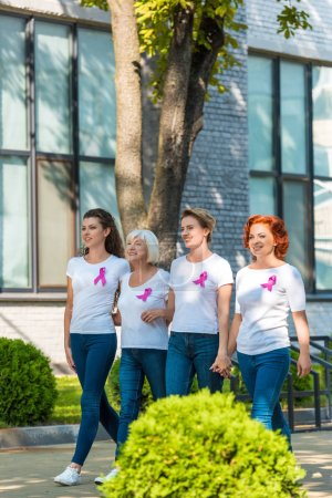 happy women with breast cancer awareness ribbons holding hands and walking together
