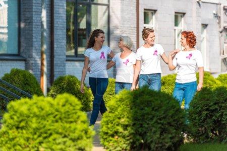 Photo pour Des femmes heureuses avec des rubans de sensibilisation au cancer du sein marchant ensemble et se souriant - image libre de droit