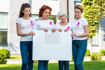 women with breast cancer awareness ribbons holding blank banner and looking down