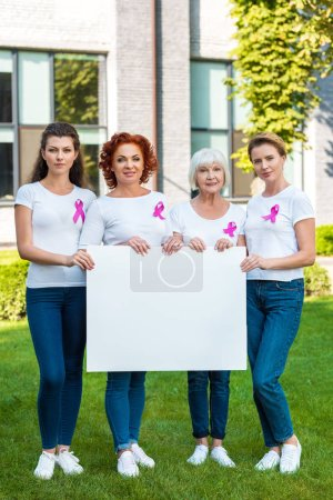women with breast cancer awareness ribbons holding blank banner and looking at camera