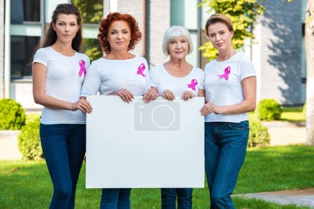 Photo for Women with breast cancer awareness ribbons holding blank banner and smiling at camera - Royalty Free Image
