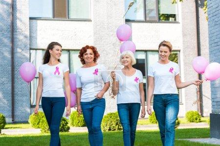 Photo pour Femmes souriantes tenant des ballons roses et marchant ensemble, concept de sensibilisation au cancer du sein - image libre de droit