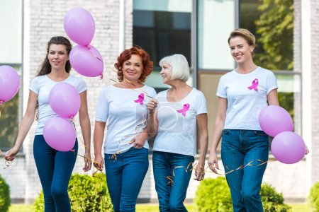 Photo for Happy women holding pink balloons and walking together, breast cancer awareness concept - Royalty Free Image