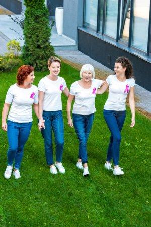 Photo pour Vue grand angle de quatre femmes souriantes avec des rubans de sensibilisation au cancer du sein marchant ensemble - image libre de droit