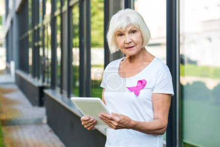 senior woman with pink ribbon on t-shirt using digital tablet and looking at camera, breast cancer awareness concept