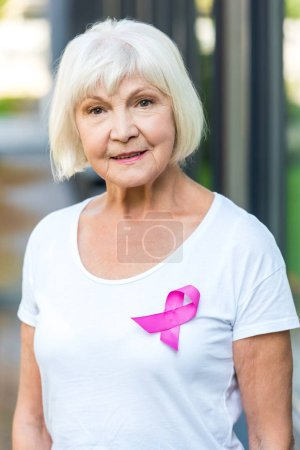 senior woman with pink ribbon on t-shirt smiling at camera, breast cancer awareness concept