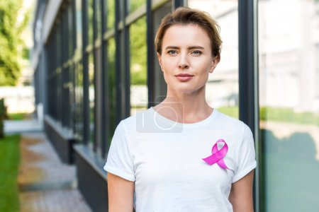 pensive middle aged woman with pink ribbon standing on street, breast cancer awareness concept