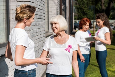 women with breast cancer awareness ribbons smiling each other outside