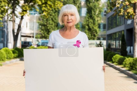 senior woman with pink ribbon holding blank card and looking at camera, breast cancer awareness concept