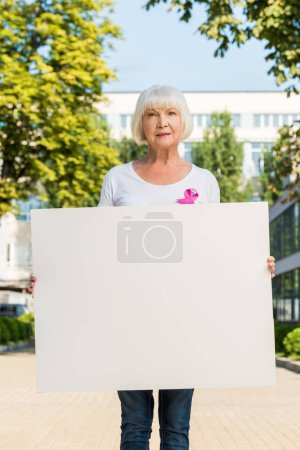 senior woman with pink ribbon holding blank banner and looking at camera, breast cancer awareness concept