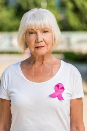 senior woman with pink ribbon looking at camera, breast cancer awareness concept