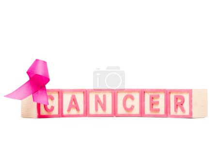 close-up view of pink ribbon and cubes with word cancer isolated on white
