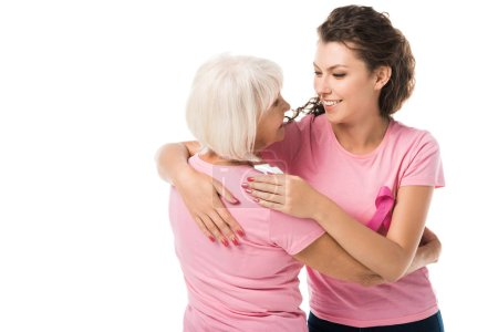 women in pink t-shirts hugging and smiling each other isolated on white, breast cancer awareness concept