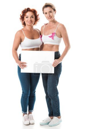 women in bras with breast cancer awareness ribbons holding blank card and smiling at camera isolated on white