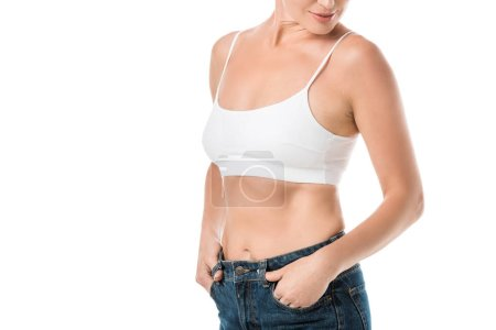 cropped shot of smiling woman in white underwear and jeans isolated on white