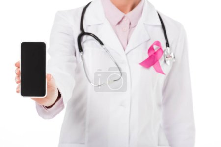 cropped shot of doctor with pink ribbon holding smartphone with blank screen isolated on white, breast cancer awareness concept