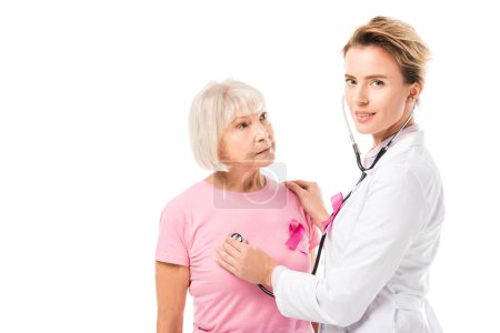 doctor with stethoscope checking health of senior woman and looking at camera isolated on white, breast cancer concept