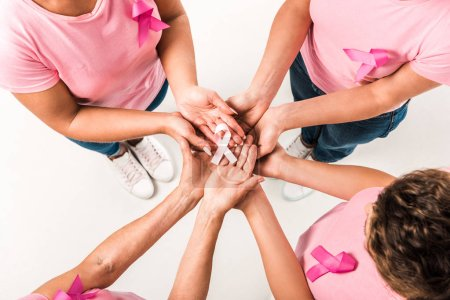 cropped shot of women in pink t-shirts holding breast cancer awareness ribbon isolated on white