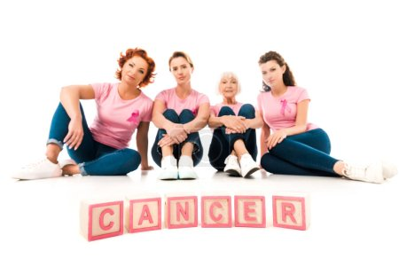 women in pink t-shirts sitting and looking at camera, word cancer isolated on white