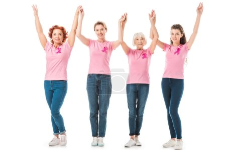 women with breast cancer awareness ribbons holding hands and smiling at camera isolated on white