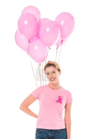 Photo pour Femme d'âge moyen tenant des ballons roses et souriant à la caméra isolée sur blanc, concept de cancer du sein - image libre de droit