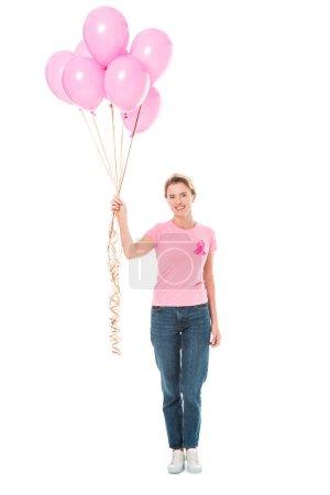 Photo pour Femme heureuse tenant des ballons roses et souriant à la caméra isolé sur blanc, concept de cancer du sein - image libre de droit