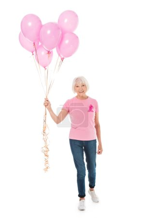 smiling senior woman holding pink balloons and looking at camera isolated on white, breast cancer awareness concept