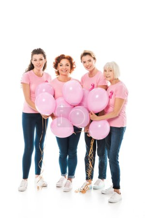 Photo pour Femmes avec des rubans de sensibilisation au cancer du sein tenant un tas de ballons roses et souriant à la caméra isolée sur blanc - image libre de droit