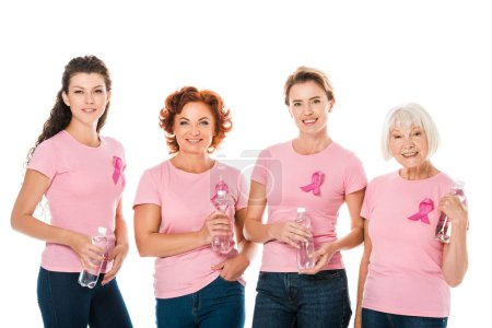 women in pink t-shirts with breast cancer awareness ribbons holding bottles of water and smiling at camera isolated on white
