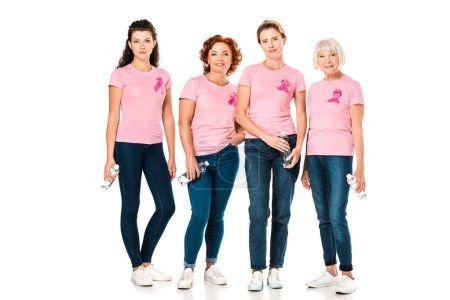 women in pink t-shirts with breast cancer awareness ribbons holding bottles of water and looking at camera isolated on white
