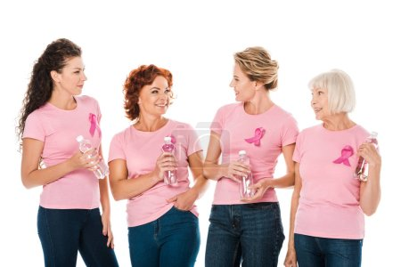 women in pink t-shirts with breast cancer awareness ribbons holding bottles of water and smiling each other isolated on white