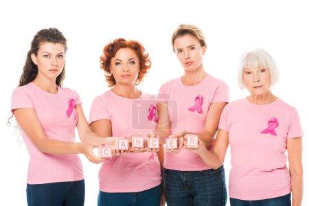 mujeres en camisetas de color rosa con cintas de conciencia de cáncer de mama que sostienen cubos con cáncer de palabra y mirando a la cámara aislada en blanco