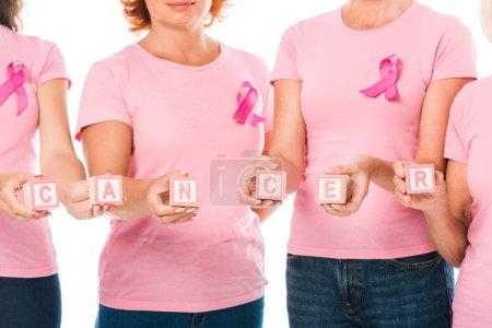 photo recadrée de femmes en rose t-shirts avec la sensibilisation au cancer du sein rubans holding cubes avec cancer de mot isolé sur blanc
