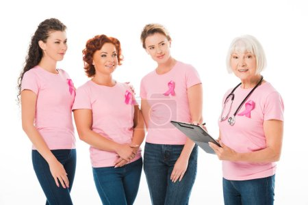 women in pink t-shirts with breast cancer awareness ribbons looking at smiling senior doctor with stethoscope and clipboard isolated on white