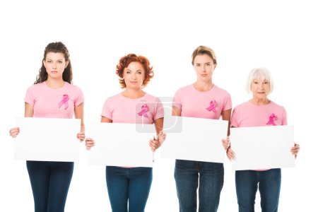 women in pink t-shirts with breast cancer awareness ribbons holding blank cards and looking at camera isolated on white
