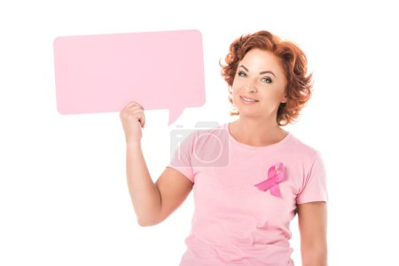 Photo for Middle aged woman in pink t-shirt with breast cancer awareness ribbon holding blank speech bubble and smiling at camera isolated on white - Royalty Free Image