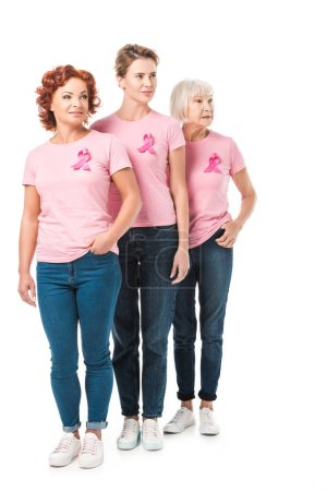 Photo pour Femmes avec des rubans roses debout ensemble et regardant loin isolé sur blanc, concept de sensibilisation au cancer du sein - image libre de droit