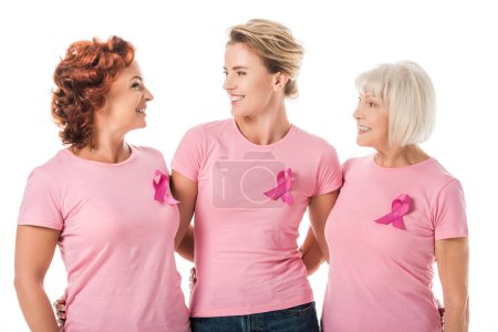 women with pink ribbons standing together and smiling each other isolated on white, breast cancer awareness concept