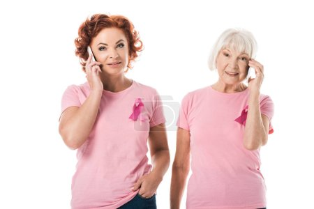 women with pink ribbons talking by smartphones and smiling at camera isolated on white, breast cancer awareness concept