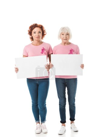 women with pink ribbons holding blank banners and looking at camera isolated on white, breast cancer awareness concept