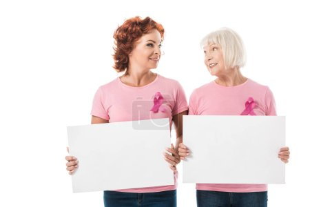 women with pink ribbons holding blank banners and smiling each other isolated on white, breast cancer awareness concept