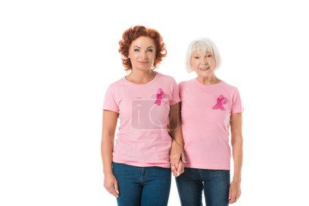 mature and senior women with pink ribbons holding hands and smiling at camera isolated on white, breast cancer awareness concept